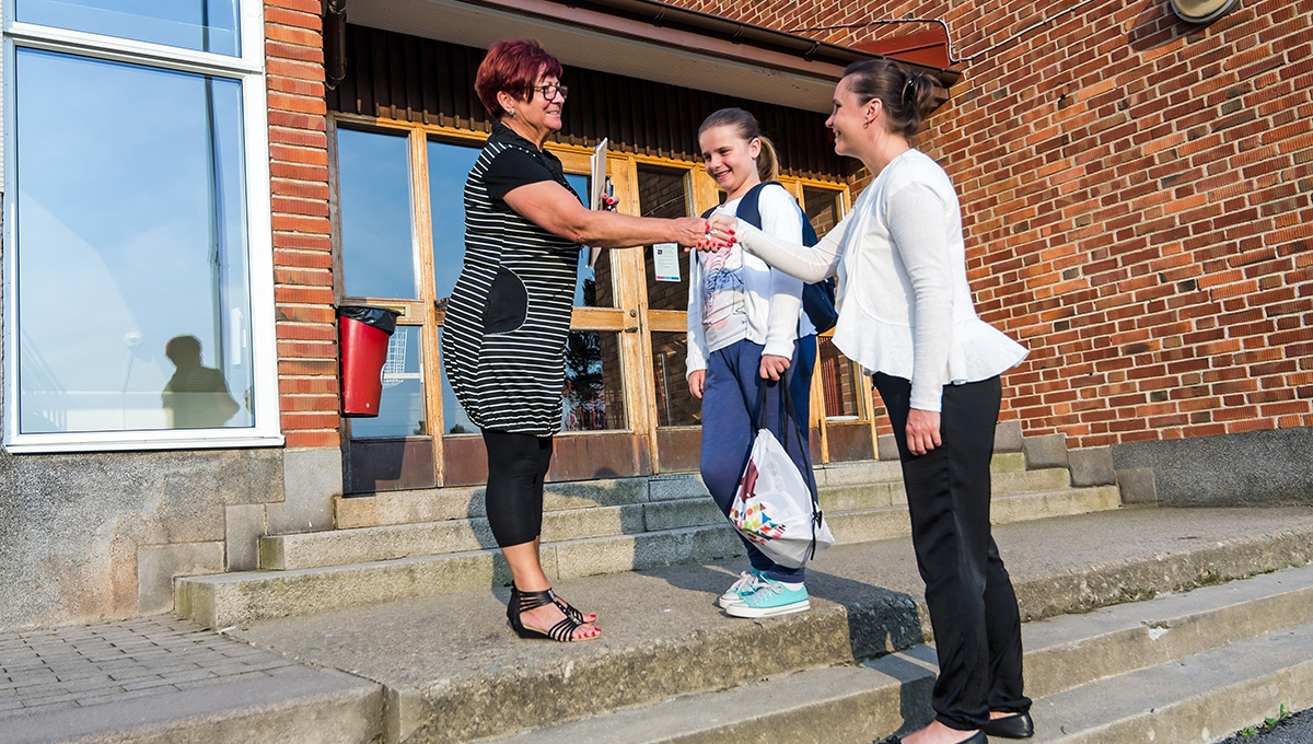 A parent, student, and teacher in conversation on the front steps of a school building