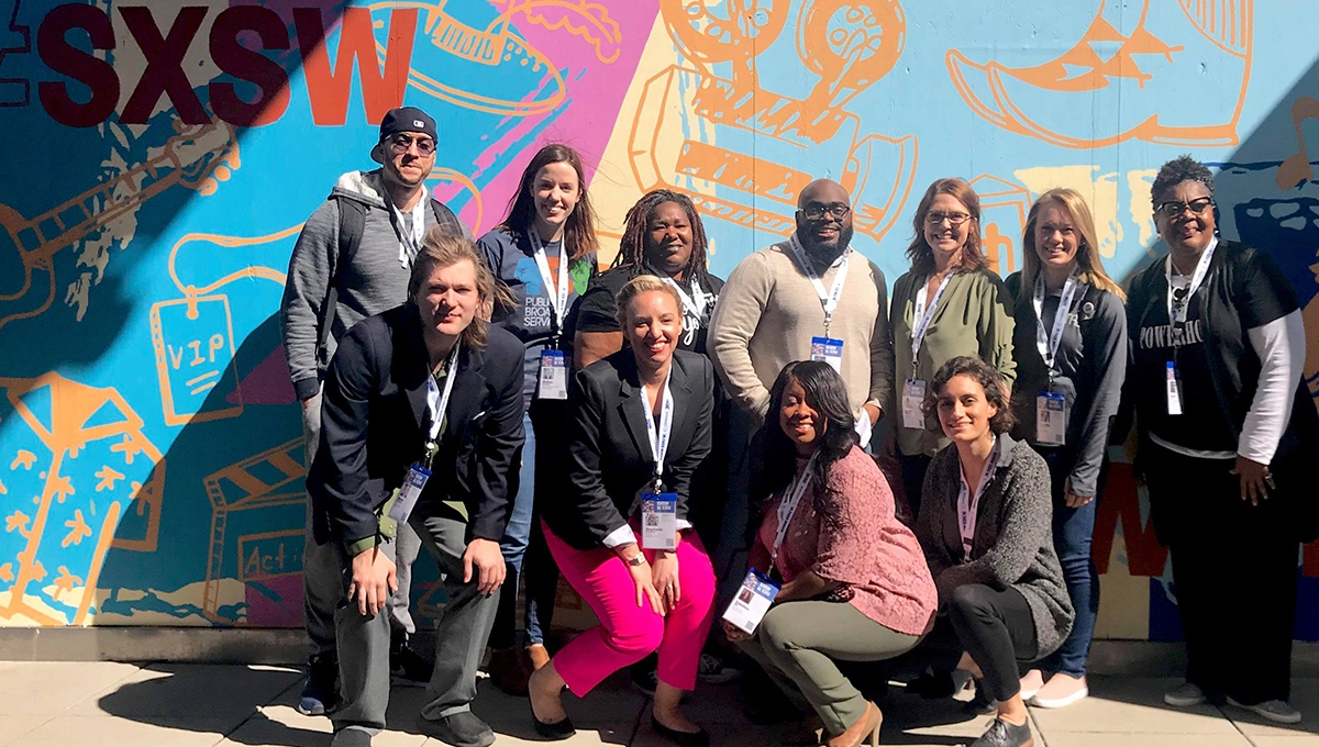 A group gathers for a photo at SXSWEDU 2018 in front of wall art in Austin, Texas.