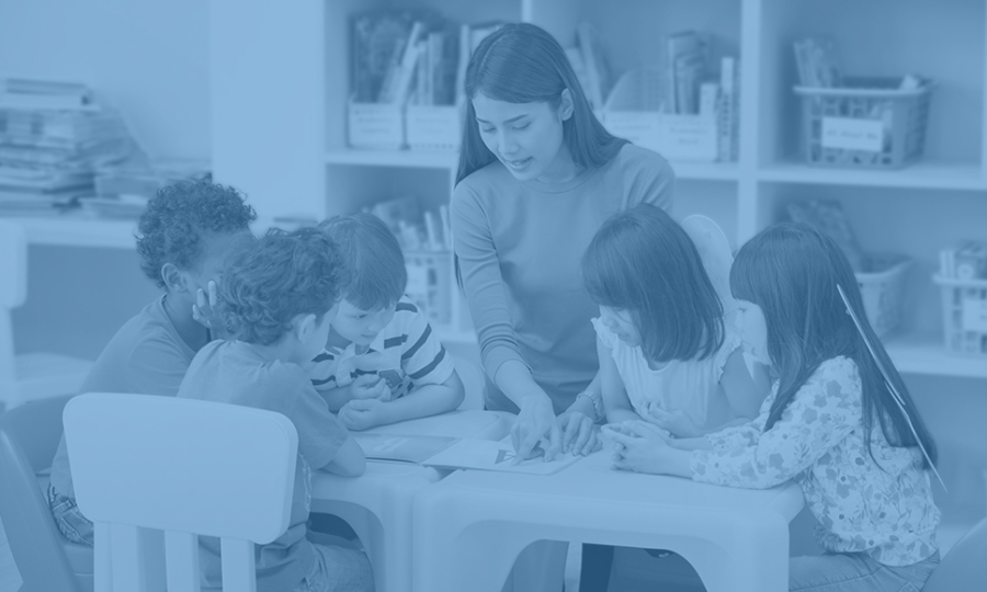 early educator teaches a group of students gathered around a table