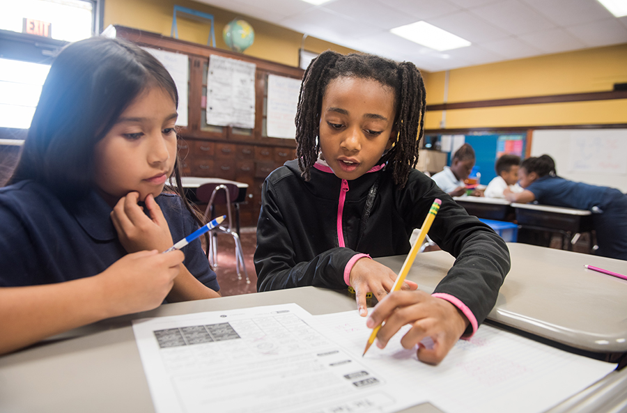 Two students fill out a worksheet in class
